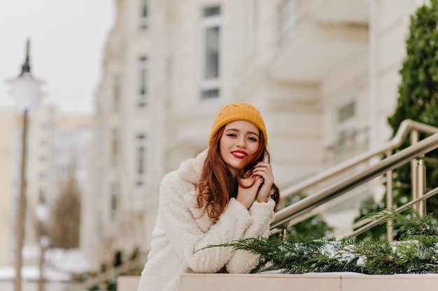 Dreamy ginger girl with bright makeup posing outdoor. portrait of elegant red-haired woman in white coat.