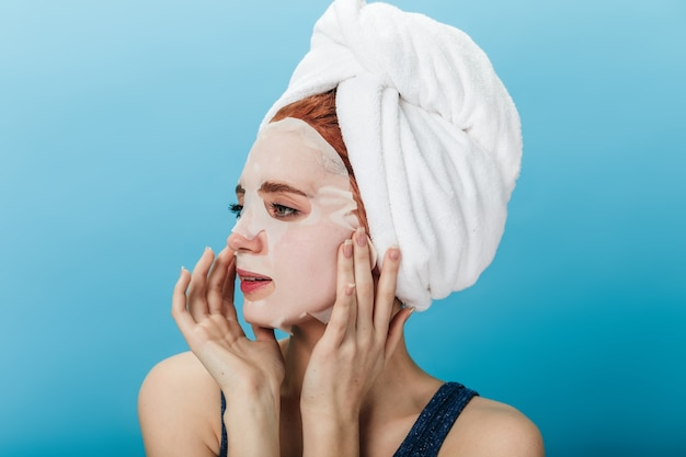 Dreamy girl applying face mask isolated on blue background. studio shot of young lady with towel on head looking away.
