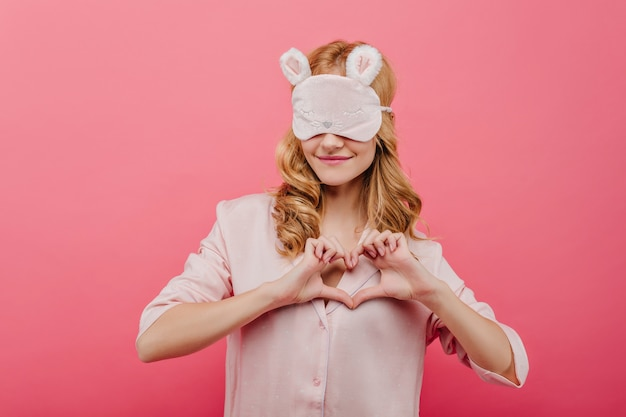 Ragazza vaga in vestito da notte carino che fa segno di amore. bello modello femminile in pigiama di seta e mascherina di sonno che gode del servizio fotografico.