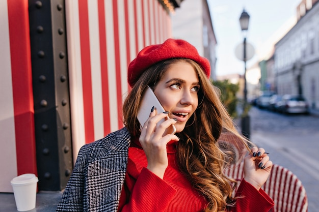 Dreamy girl in cute red beret plays with dark hair while talking on phone