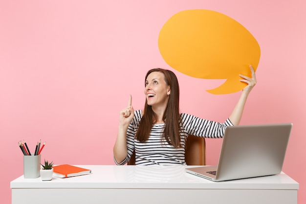 Dreamy girl holding yellow empty blank say cloud speech bubble work at white desk with pc laptop isolated on pastel pink background. achievement business career concept. copy space for advertisement.