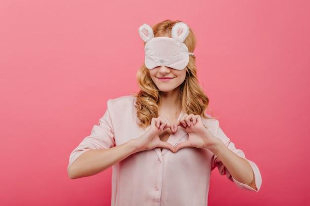 사랑 기호를 만드는 귀여운 잠 옷에 꿈꾸는 소녀. 실크 파자마와 사진 촬영을 즐기는 수면 마스크의 아름다운 여성 모델.