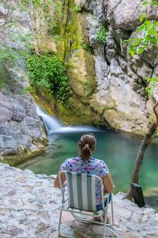 A dreamy girl is meditating in a green lagoon near a waterfall.