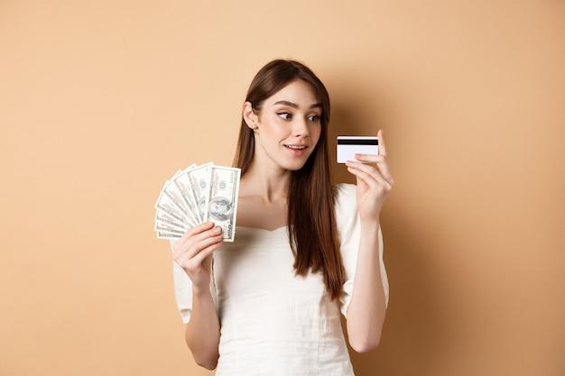 プラスチック製のクレジットカードを見て、買い物を考えて、ドル札を持って、ベージュの背景に立っている夢のような女の子。