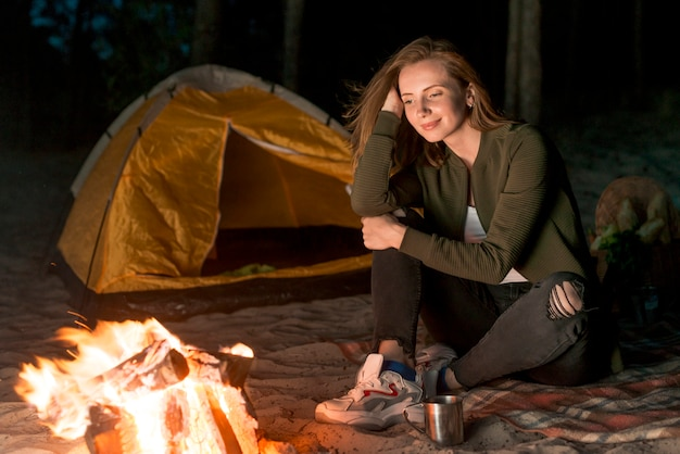 Dreamy girl looking at the campfire