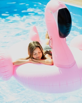 Dreamy girl sitting on a flamingo floatie