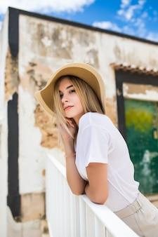 Ragazza vaga che si siede sulla terrazza in cappello di paglia e occhiali da sole.