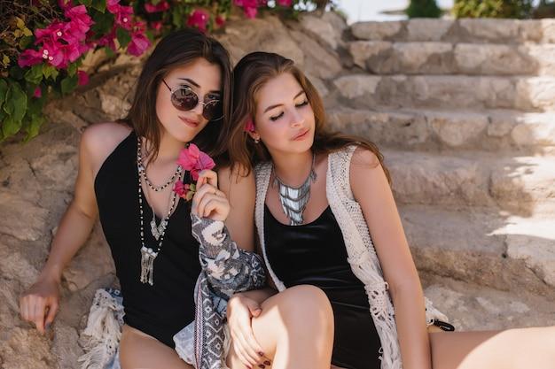 夢のような女の子が友人の足に触れ、目でポーズをとって、夏の朝を屋外で楽しんでいます。海で泳いだ後、石の階段で休んでいる黒い服を着た素敵な日焼けした姉妹