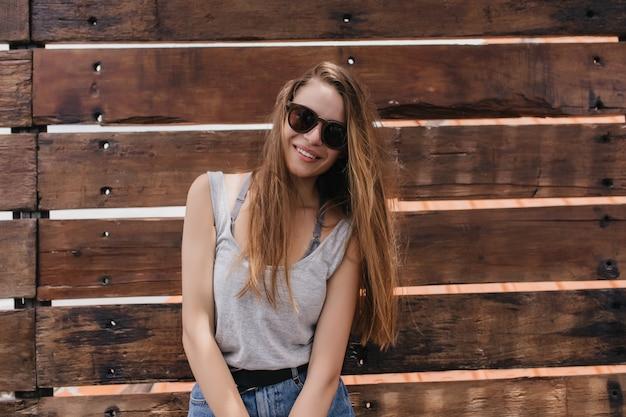 귀여운 미소로 나무 벽 근처 포즈를 취하 긴 갈색 머리를 가진 꿈꾸는 소녀. 여름 옷에 평온한 유럽 모델의 초상화.