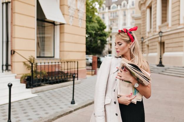 短いブロンドの髪を持つ夢のような女の子は新聞を買ってそれを読むために家に帰ります