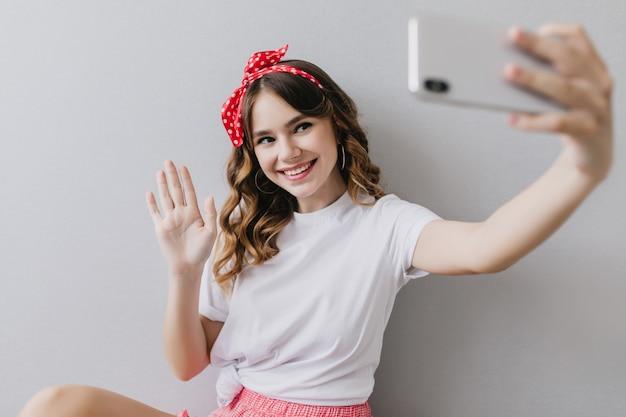 笑顔でポーズをとるウェーブのかかった髪型の夢のような女の子。セルフィーを作る白いカジュアルなtシャツを着た素晴らしい若い女性の屋内ショット。