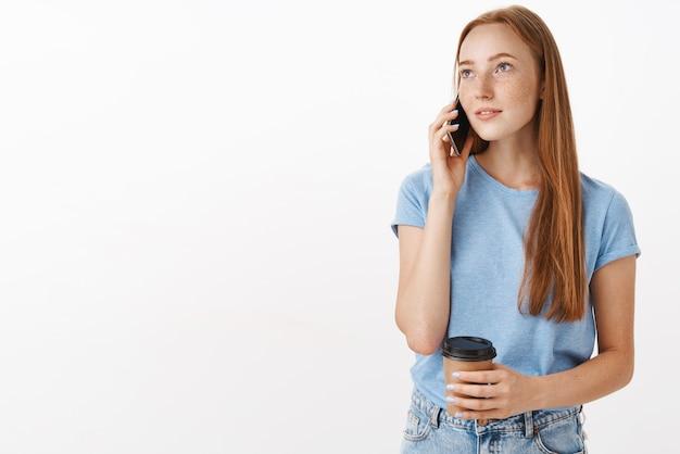 Мечтательная красивая женщина с расслабленным взглядом держит бумажный стаканчик с кофе во время разговора по телефону