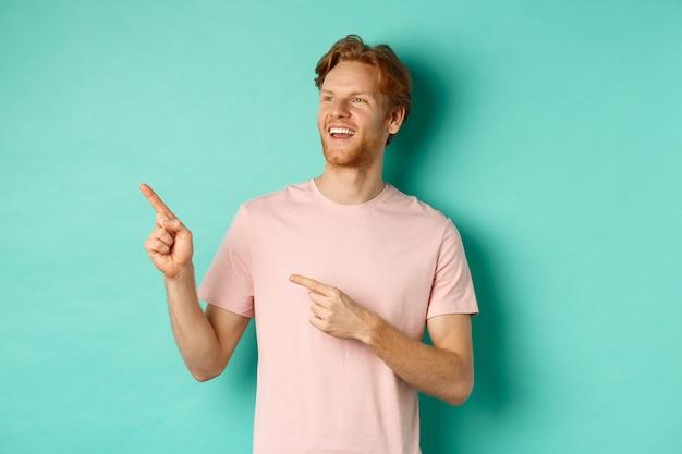 赤い髪の夢のようなハンサムな男は、笑顔で左上隅を畏敬の念を持って見て、何かを賞賛し、ミントの背景の上に立っています。コピースペース