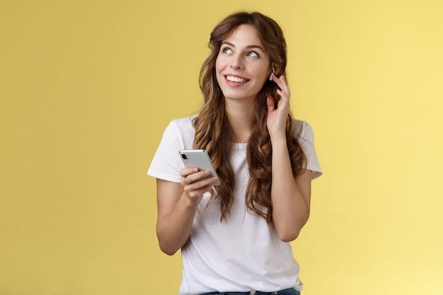 Мечтательная счастливая веселая кудрявая девушка оглядывается, созерцает прекрасную летнюю погоду, слушая музыку, сенсорный беспроводной наушник, вызывающий друга, разговаривает через наушники, держит смартфон, желтый фон