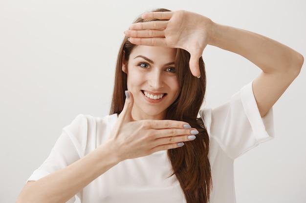 Мечтательная счастливая женщина делает жест кадры, улыбаясь веселый