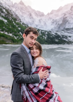 Dreamy honeymoon of just married couple in love in the winter mountains and picturesque frozen lake