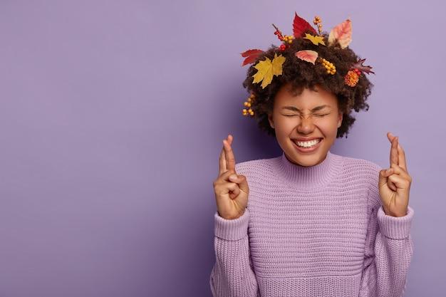 夢のような希望に満ちたアフリカ系アメリカ人の女の子は、勝利を信じ、秋の時期に祈り、ニットのジャンパーを着て、紫色の壁に孤立した巻き毛の葉を持っています