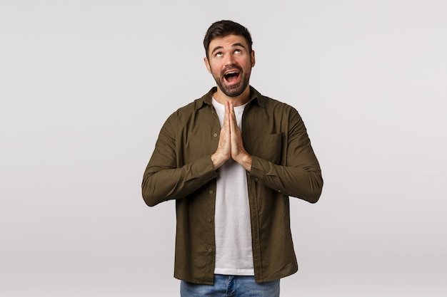 Dreamy, hopeful cute caucasian bearded man believe god, want dream come true, press palms together over chest, hope wish fulfill, looking up happy and optimistic, anticipate relish good deal