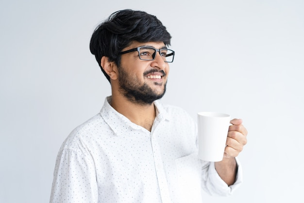 Dreamy indian man holding mug. smiling young guy drinking tea or coffee.
