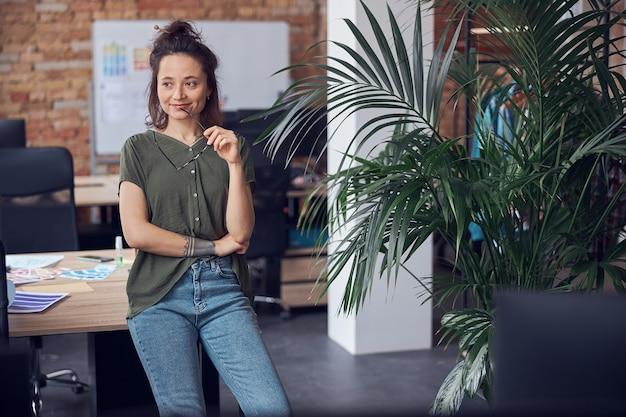 Мечтательная женщина-дизайнер интерьера держит очки и улыбается, стоя в современном зеленом