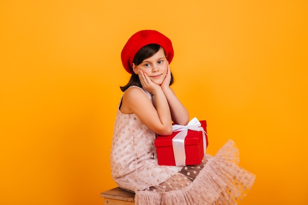 誕生日プレゼントでポーズをとる夢のような子供。新年の贈り物を保持している赤いベレー帽のプレティーンの女の子。