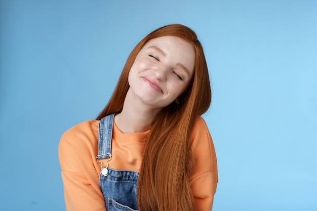 Dreamy kind silly redhead smiling happy girl straight long ginger hair daydreaming imagine romantic moment close eyes smiling delighted tilting head look joyful standing blue background