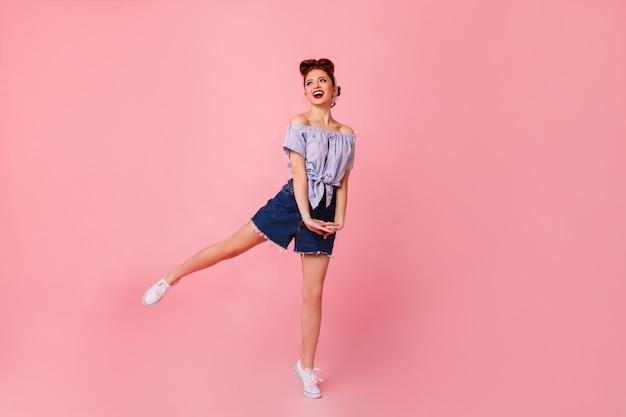 笑顔で踊るデニムショートパンツの夢のような女性。ピンクの空間にジャンプする美しいピンナップガール。