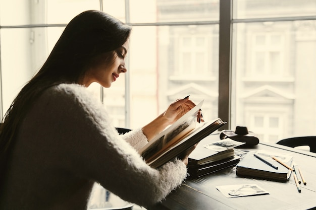 夢のような女性は、カフェの古い写真アルバムで座っている