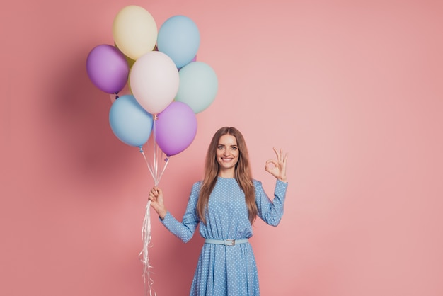 Dreamy lady with many air balloons show okey sign on pink background