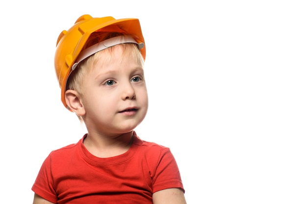 Dreamy little blond boy in a construction helmet and a red t-shirt.