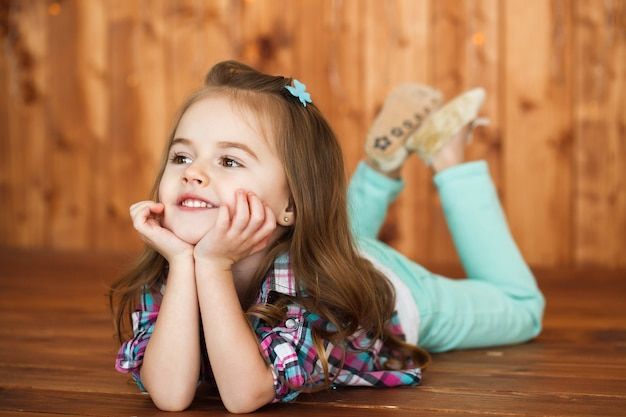 Dreamy little girl lies on wooden floor and holds her chin on palms