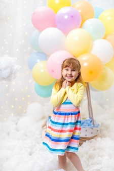 Dreamy little girl stands in clouds on with decorative balloon basket