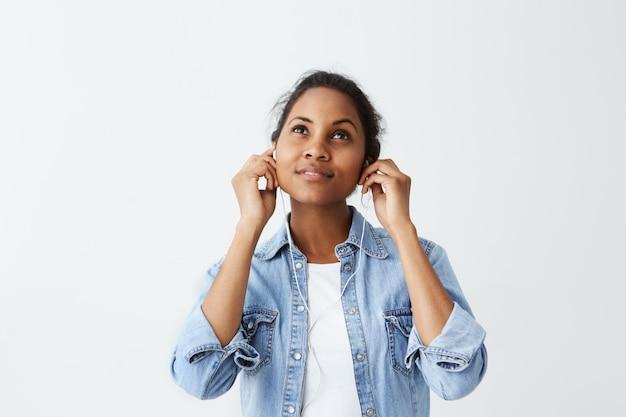 Bella donna afroamericana sembrante vaga con capelli neri in camicia blu che indossa le cuffie, ascoltando musica, usando l'app di musica sul suo smartphone.