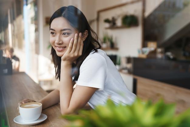 혼자 도시 카페에 앉아 커피를 마시는 캐주얼 흰색 티셔츠에 꿈꾸는 사랑스러운 아시아 소녀.