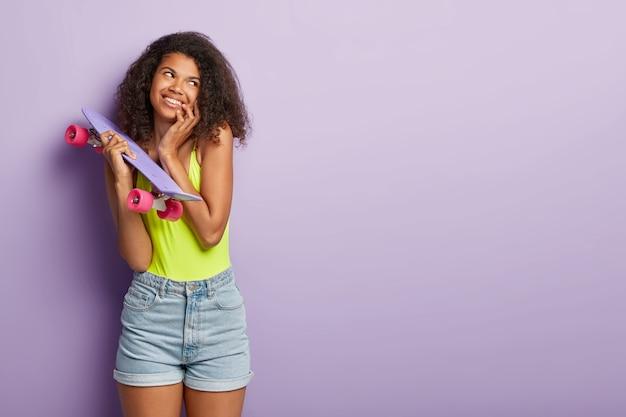 Bella ragazza adolescente sognante con acconciatura afro, guarda da parte con piacere