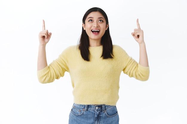 Мечтательная счастливая азиатская девушка чувствует себя взволнованной и счастливой, получает отличный шанс, показывает пальцем вверх на мечту, которая сбылась, улыбается, жизнерадостная, стоящая белая стена изумлена, радуясь хорошим новостям