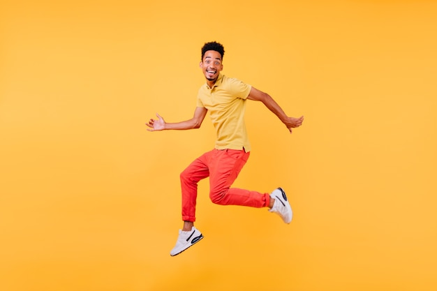 Dreamy male model with brown skin fooling around. indoor shot of african guy in bright clothes jumping.