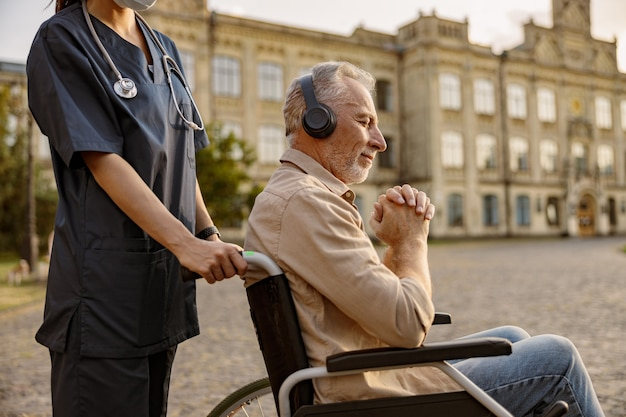 Dreamy mature handicapped man in wheelchair wearing headphones and listening to music with eyes