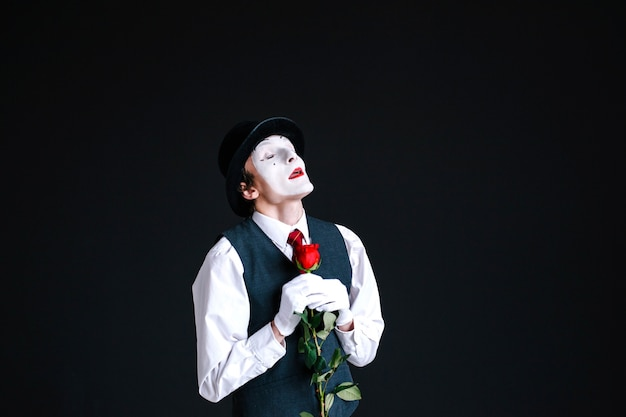 Dreamy mime stands with red rose on black background
