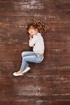 Мечтательная девушка настроения, свернувшись калачиком, лежа на полу, глядя в сторону и улыбаясь