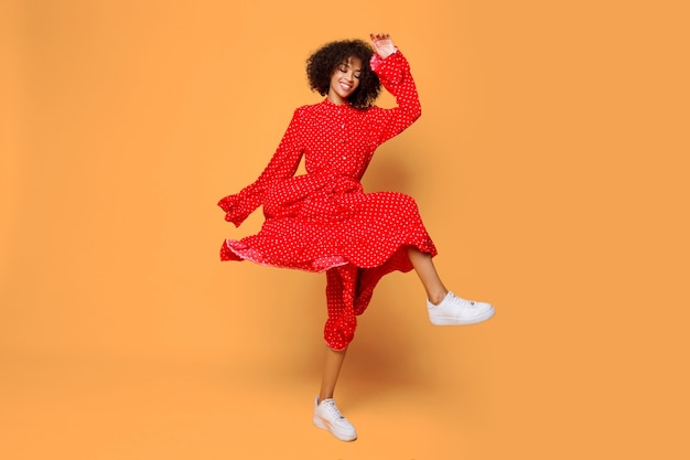Dreamy mood. stylish african girl dancing and jumping on orange