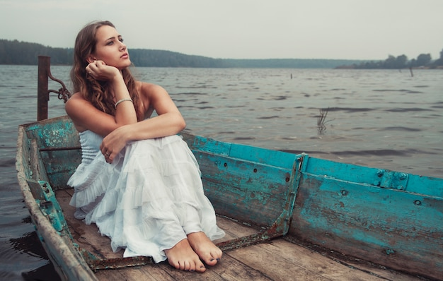 Dreamy mysterious blonde girl white dress in boat