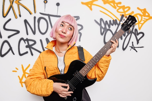 Dreamy pink haired pretty teenage girl plays electric acoustic guitar performs her favorite song enjoys free lifestyle wears orange jacket poses against graffiti wall wants to be popular rocker