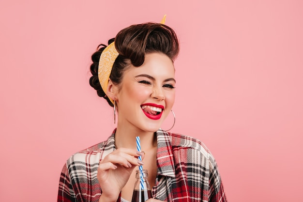 Dreamy pinup girl with bright makeup laughing on pink background. studio shot of carefree lady drinking beverage.