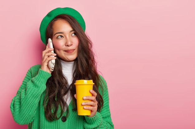 Dreamy pleasant looking asian girl holds smartphone near ear, enjoys pleasant conversation while drinks coffee to go, has long dark hair, dressed in green stylish clothes
