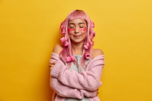 Donna dall'aspetto sognante e piacevole con i capelli rosa, si abbraccia delicatamente, gode della morbidezza del maglione caldo, indossa i bigodini, rende l'acconciatura perfetta