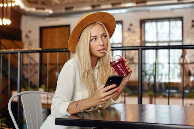 Giovane donna bionda dai capelli lunghi dall'aspetto piacevole sognante con pausa pranzo nella caffetteria moderna, in attesa del suo ordine e tenendo lo smartphone in mano, vestito con abiti alla moda