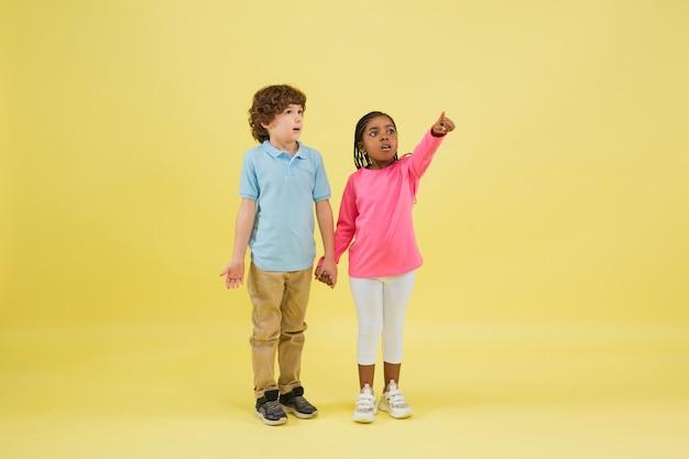 夢のようなポインティング。黄色の背景に孤立したかわいい子供たち。