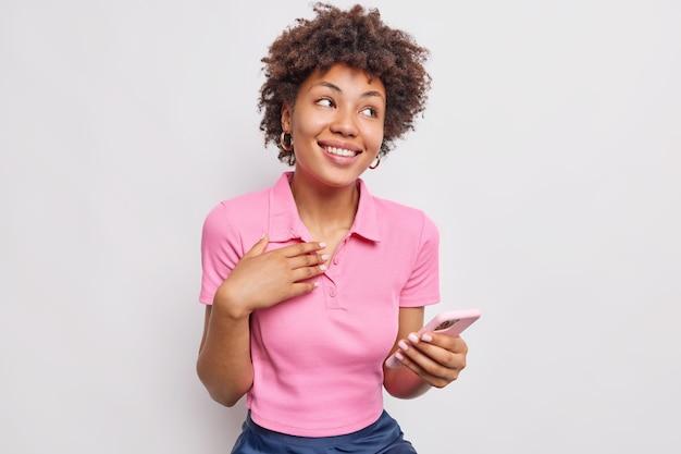 夢のようなポジティブな巻き毛のアフロアメリカ人女性は、白い壁に隔離されたカジュアルなtシャツを着て快適にスマートフォンの笑顔で写真を表示しながらロマンチックな瞬間を思い出します