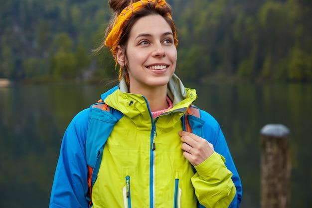 꿈꾸는 긍정적 인 여성 여행자는 활동적인 레크리에이션을하고 녹색 숲과 호수에서 포즈를 취하고 캐주얼 한 옷을 입습니다.